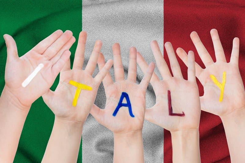 De inschrijving van Italië op de handen van de kinderen tegen de achtergrond van een golvende vlag van Italië stock afbeeldingen