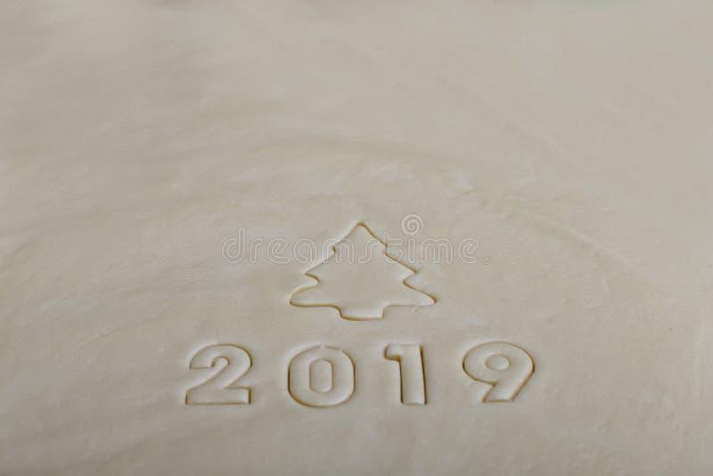 De inschrijving in de vorm van 2019 op het ruwe die deeg, van vormen voor koekjes wordt gestempeld Het symbool van komende 2019 royalty-vrije stock foto