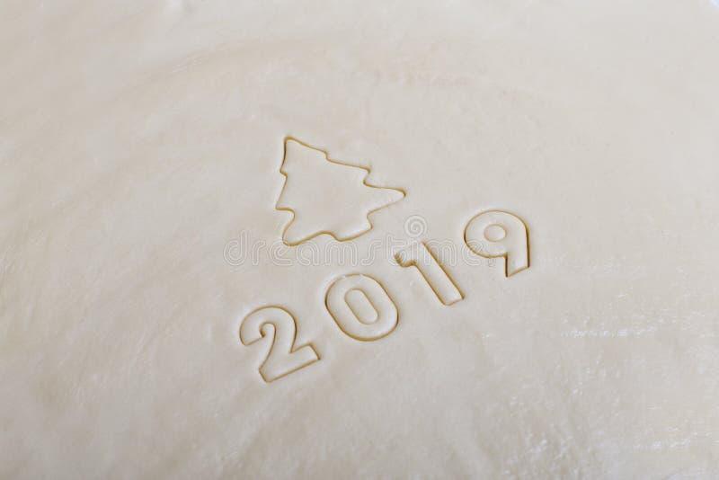 De inschrijving in de vorm van 2019 op het ruwe die deeg, van vormen voor koekjes wordt gestempeld Het symbool van komende 2019 stock afbeeldingen