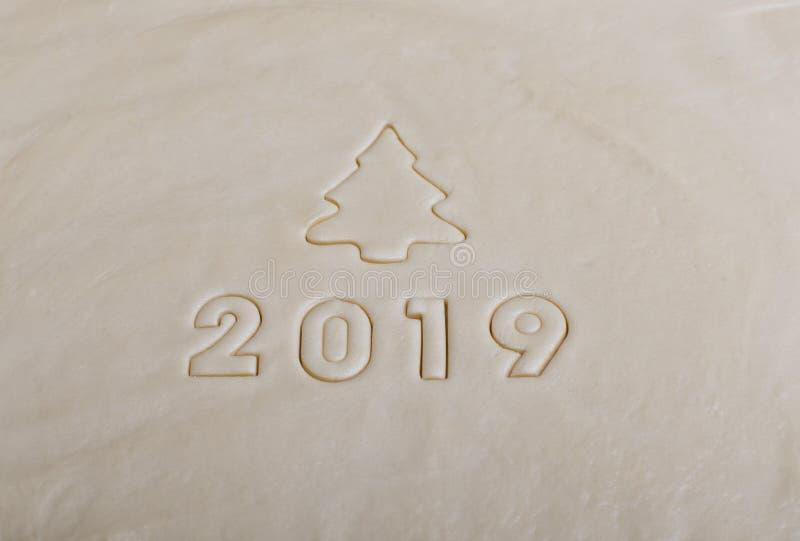 De inschrijving in de vorm van 2019 op het ruwe die deeg, van vormen voor koekjes wordt gestempeld Het symbool van komende 2019 stock foto