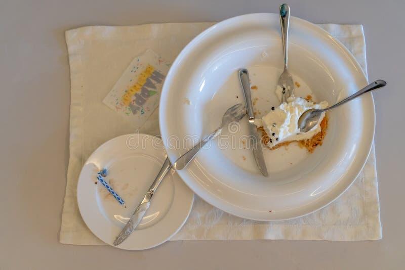 De inschrijvings gelukkige verjaardag Cakegift van het hotel Resterende cake op een vuile plaat De vakantie is over stock foto's