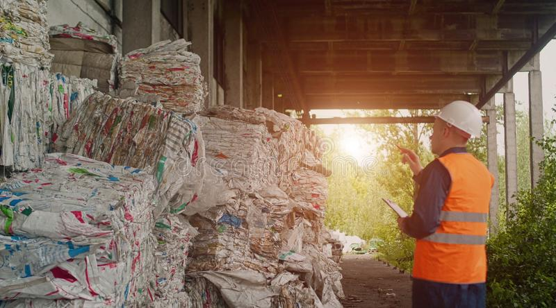 De inspecteur controleert het gedrukte huisvuil bij de afval recyclingsinstallatie, afval recycling, zonsondergang stock afbeelding