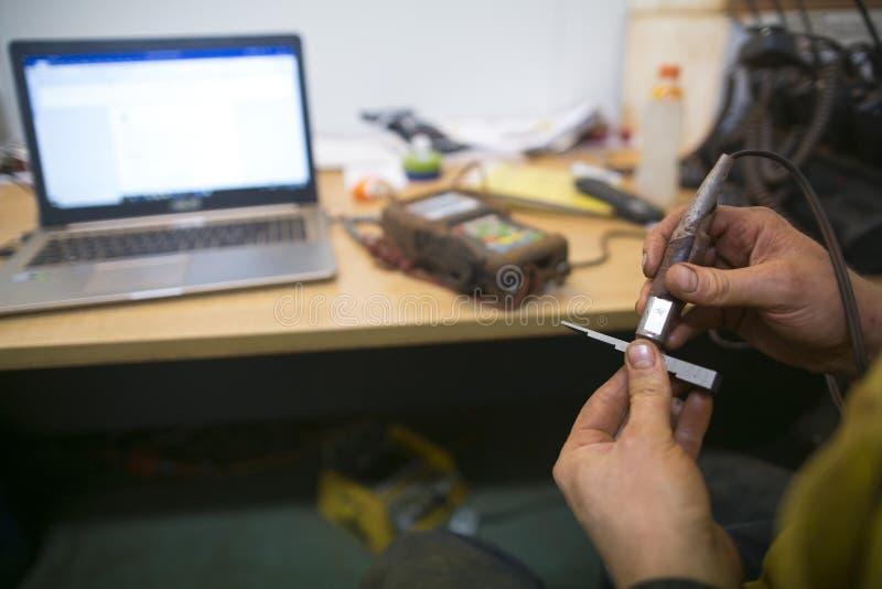 De inspecteur die van de kabeltoegang abseiler het uitvoeren van het inspecteren het kalibreren UT plaatsen de vastgestelde Niet  stock afbeeldingen