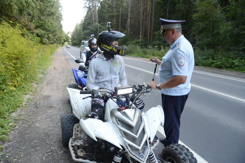 De inspecteur van de patrouille van de wegpolitie hield de ATV-bestuurders voor het controleren tegen stock foto's