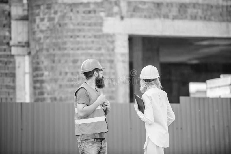De inspectie van de bouwwerfveiligheid Bespreek vooruitgangsproject Het concept van de veiligheidsinspecteur Vrouweninspecteur en royalty-vrije stock afbeeldingen