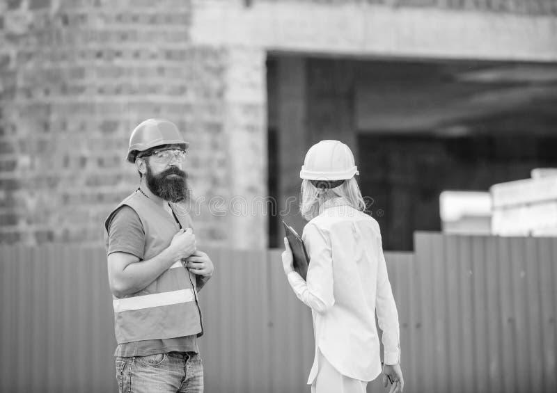 De inspectie van de bouwwerfveiligheid Bespreek vooruitgangsproject De vrouweninspecteur en de gebaarde brutale bouwer bespreken stock foto's