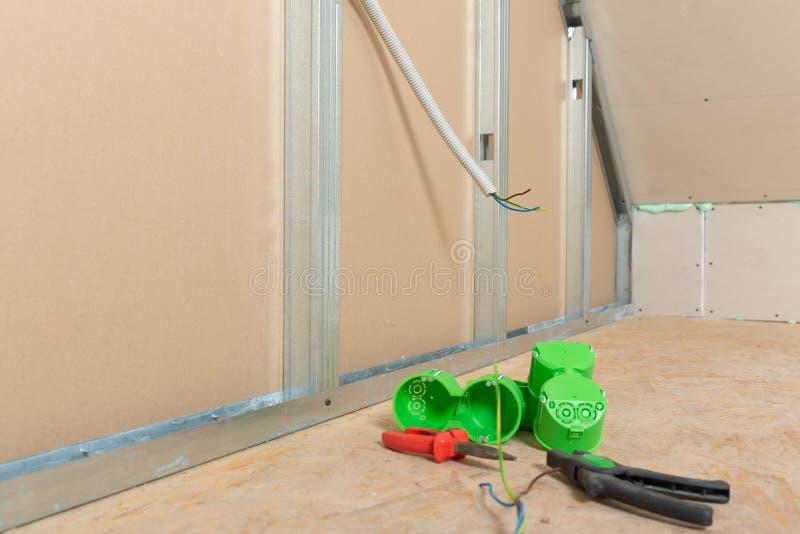 De installatie van de elektriciteitsdraad in gipsplaatmuur in zolder Zoldervernieuwing stock fotografie