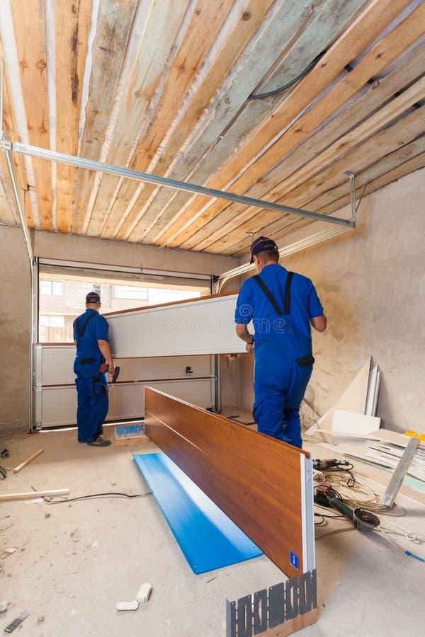 De installatie van garagedeuren Arbeiders die opheffend systeem installeren stock fotografie