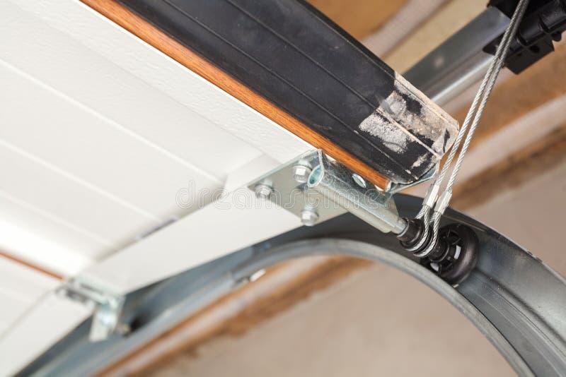 De installatie van garagedeuren Sluit omhoog van het opheffen van systeem in metaal profil stock afbeeldingen