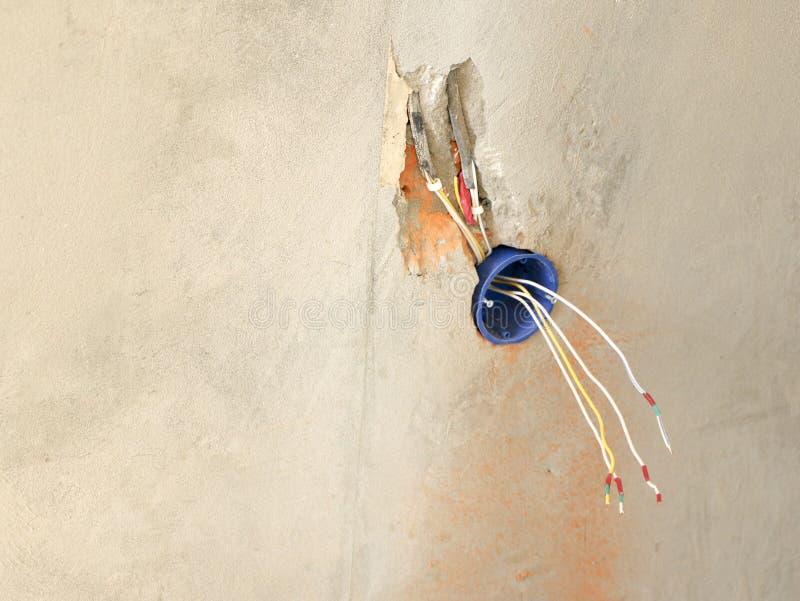 De installatie van de muurcontactdoos Het werk bij het installeren van elektroafzet De elektricien bereidt de afzet van de bedrad stock foto's