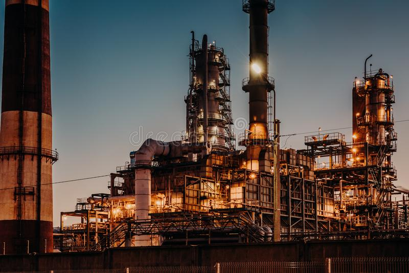 De installatie van de olieraffinage bij nacht met lichten Staalpijpleidingen en schoorstenen Aardolie en energie het concept van  stock afbeeldingen