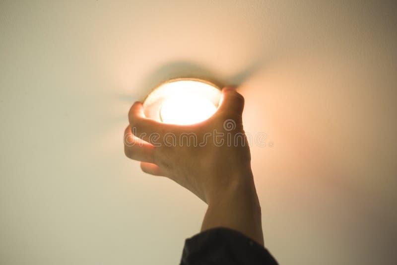 De installatie van puntlicht, hand neemt de lamp in het plafond op stock foto