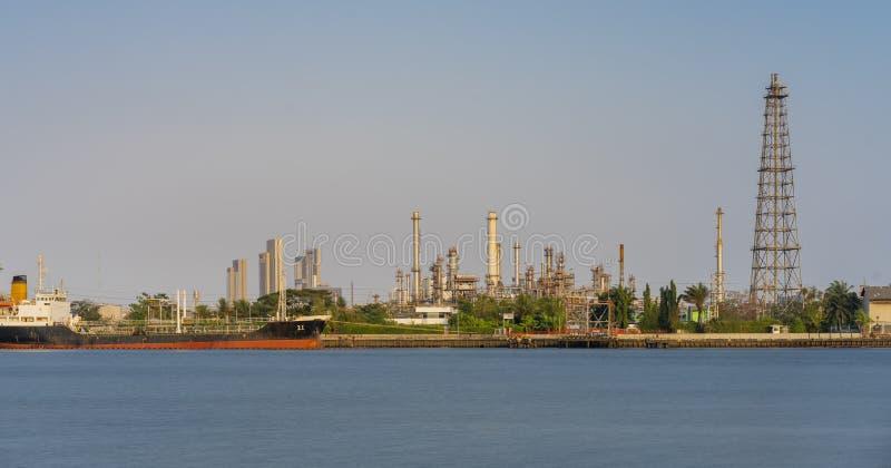 De installatie van de ruwe olieraffinaderij en vele schoorsteen met petrochemische tanker of vrachtschip bij kust van rivier op d royalty-vrije stock afbeelding