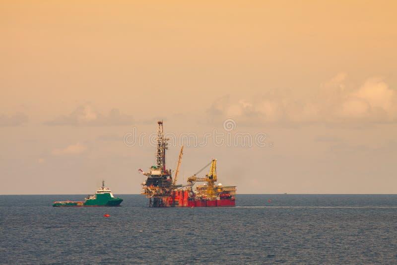 De installatie voor productieolie en gas in zee, Installatieplatform die aan het platform voor het boren werken en vindt olie en  stock foto