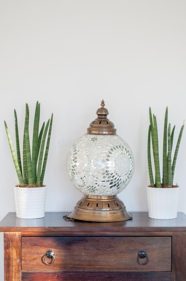De installaties en een decoratieve Griekse lamp op een houten lade in ontspannen stock afbeeldingen