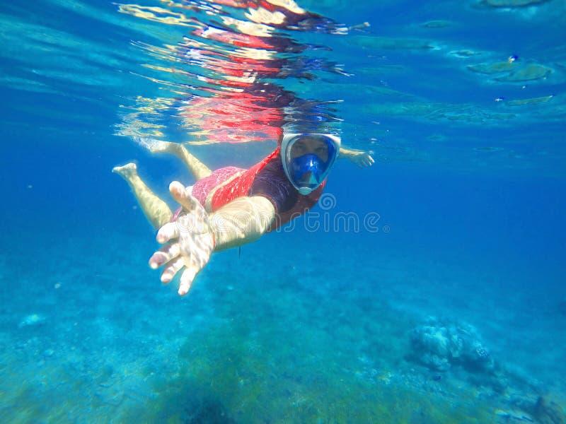 De instructeur snorkelt geeft de hand voor hulp, het snorkelen les, het snorkelen instructeur stock afbeelding