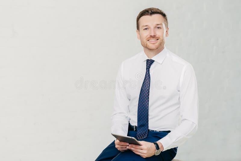 De intelligente advocaat in elegante kleren, houdt digitale tablet, doorbrengt vrije tijd in bureau, heeft prettige glimlach op o stock foto's