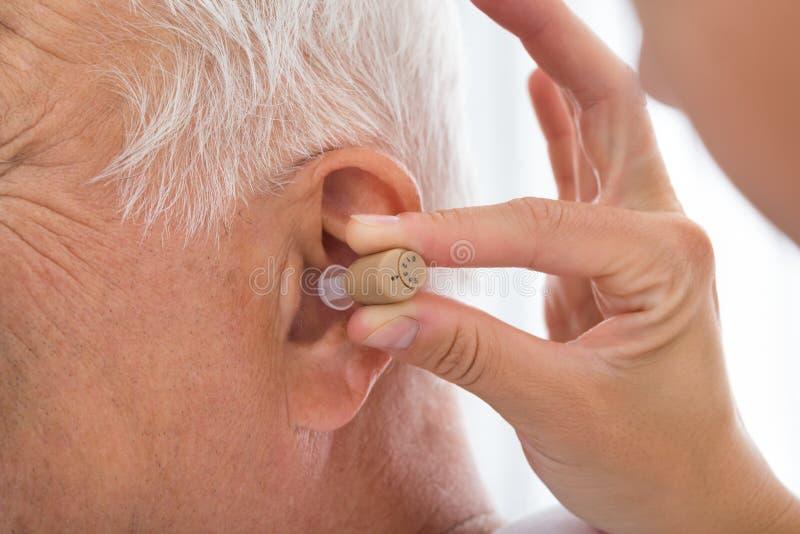 De Intern verpleegde patiënt` s Oor van artsenputting hearing aid stock afbeeldingen