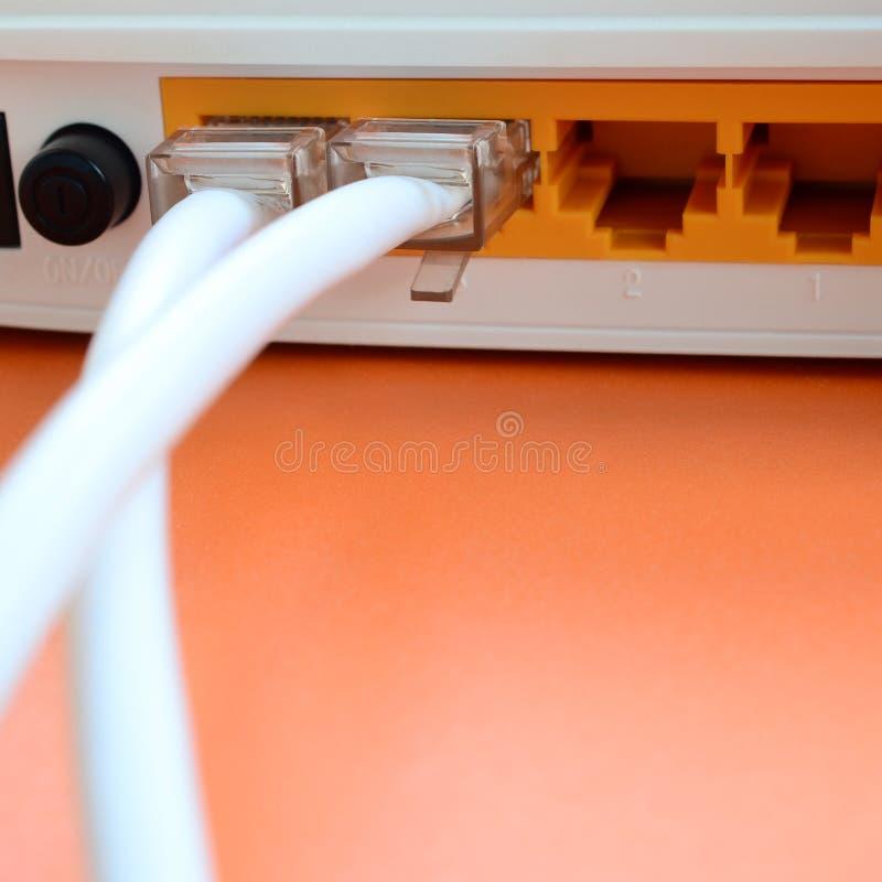De Internet-kabelstoppen worden verbonden met de Internet-router, w stock afbeeldingen