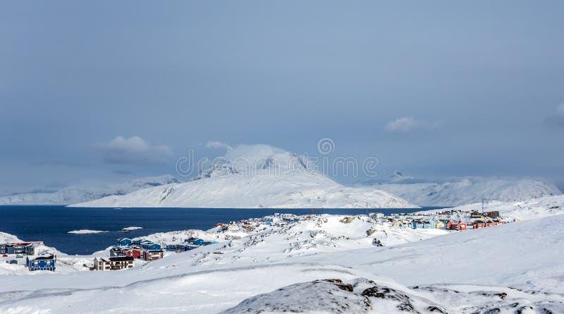 De de Inuithuizen en plattelandshuisjes verspreidden zich over het landschap van de sneeuwtoendra in woonvoorstad van Nuuk-stad m stock foto's