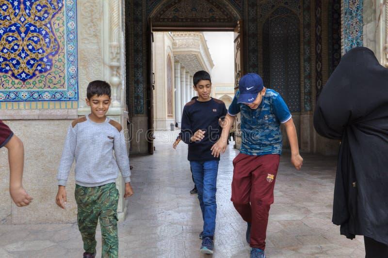 De Iraanse pas van jongenstienerjaren door grote poort van moskee, Iran stock foto's