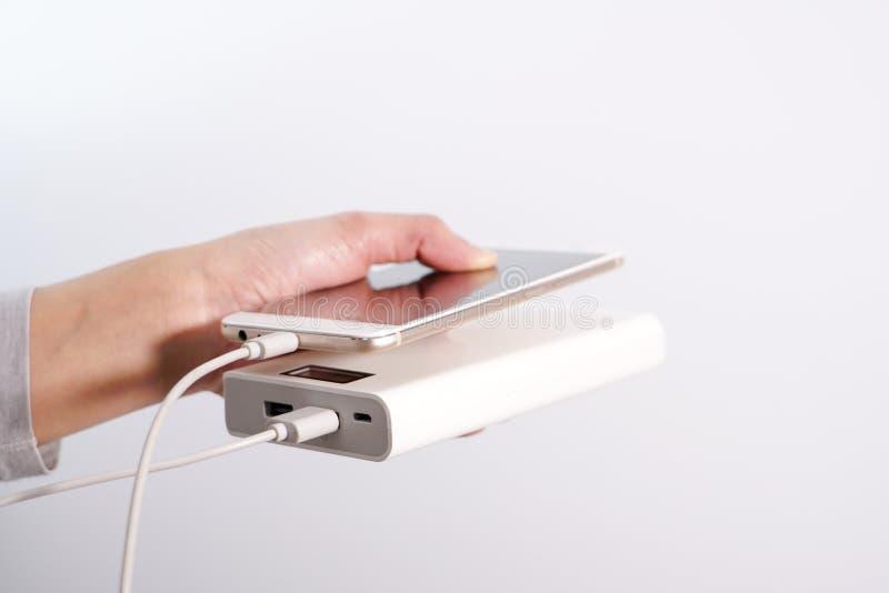 De isolate vrouwenhand houdt de telefoon en de lader, powerbank en de slimme telefoon verbindt, energie stock foto
