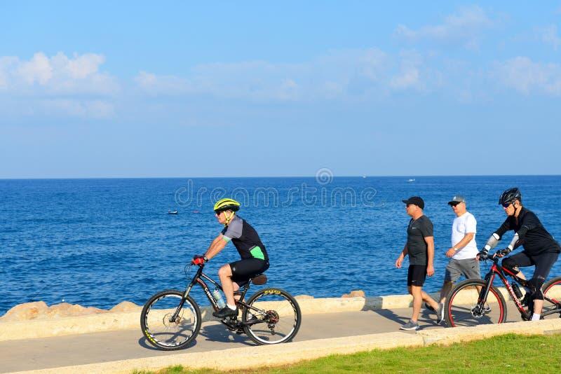 De Israëlische bejaarden berijden een fiets langs het strand van Tel Aviv stock afbeelding