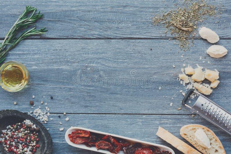 De Italiaanse achtergrond van keukeningrediënten op blauw rustiek hout, exemplaarruimte stock afbeeldingen