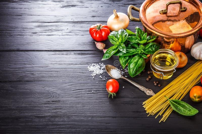 De Italiaanse deegwaren van de voedselvoorbereiding op houten raad stock foto's