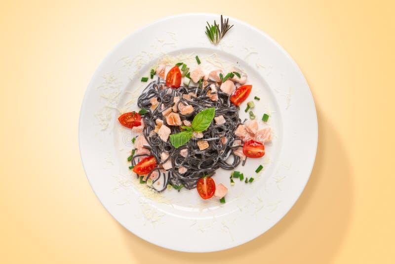 De Italiaanse deegwaren van de pijlinktvisinkt met zalm en parmezaanse kaaskaas voedsel van hierboven royalty-vrije stock afbeeldingen