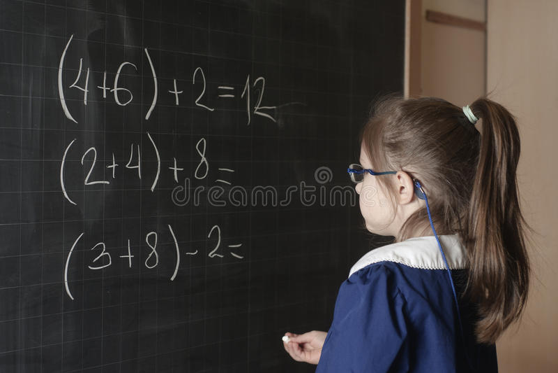 De Italiaanse eerste-nivelleermachine van het basisschoolmeisje lost wiskunde op stock afbeelding