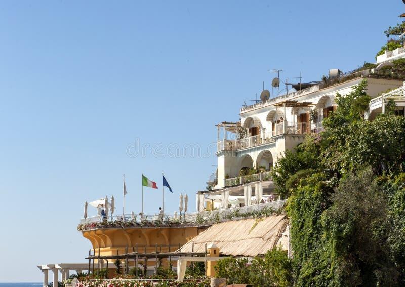 De Italiaanse vlag en twee anderen vliegen over een het dineren gebied die de Baai van Salerno, Positano overzien, stock foto