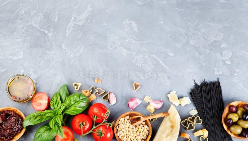 De Italiaanse voedselachtergrond met wijnstoktomaten, basilicum, spaghetti, parmezaanse kaasingrediënten op steen dient Exemplaar stock afbeeldingen