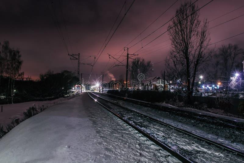 De järnväg linjerna och stångnärbilden nära järnvägsstationen som bort går till avståndet Vinterseasonr arkivbild
