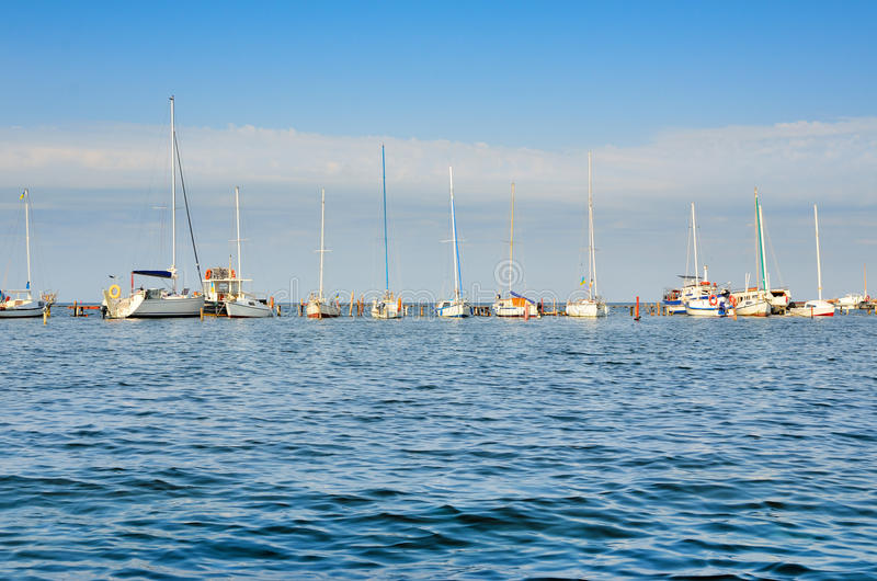 De jachten en de varende boten zijn op het dok De kleine zeeschepen zijn in de haven op een achtergrond van blauwe hemel royalty-vrije stock afbeelding