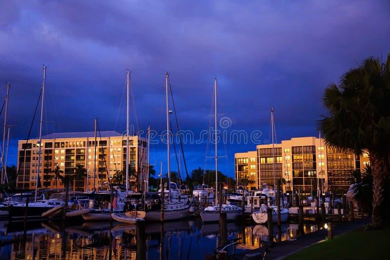 De jachthavengemeenschap van Florida Flatgebouwen met koopflats bij blauw uur die boten in een jachthaven overzien stock afbeeldingen