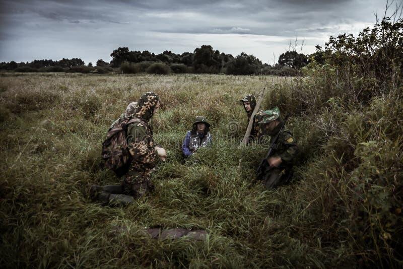 De jachtscène met groep jagers op landelijk gebied met dramatische hemel in verwachting van de jacht in lang gras tijdens jachtse stock foto's