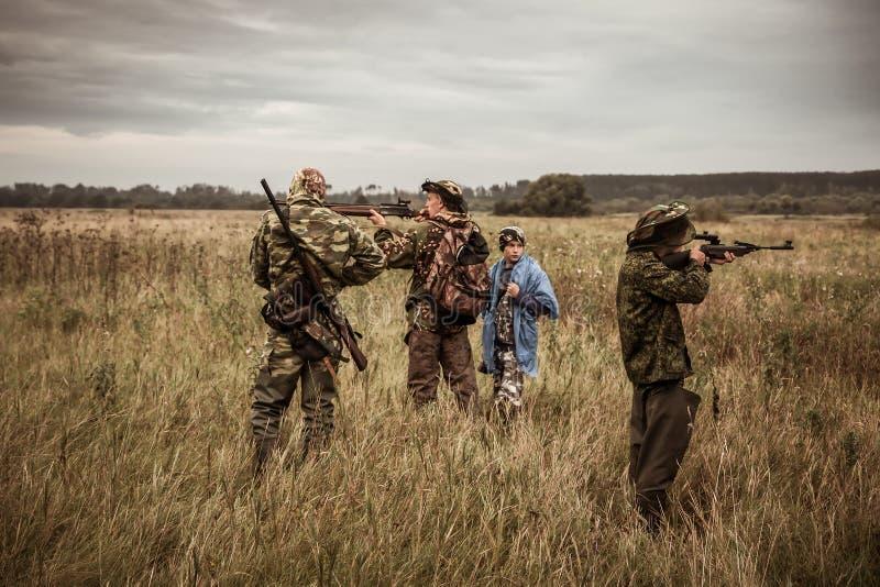 De jachtscène met jagers die tijdens jachtseizoen op landelijk gebied in donkere dag met humeurige hemel streven royalty-vrije stock fotografie
