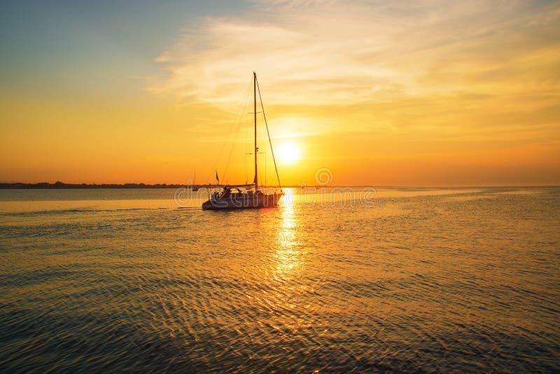 De jachtzeilen aan de pijler Overzeese zonsondergangtijd stock afbeelding