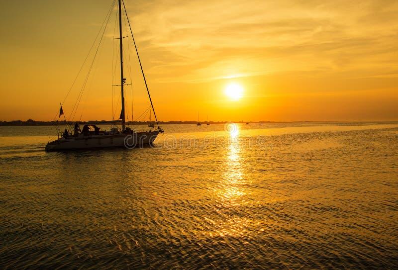 De jachtzeilen aan de pijler Overzeese zonsondergangtijd stock afbeeldingen