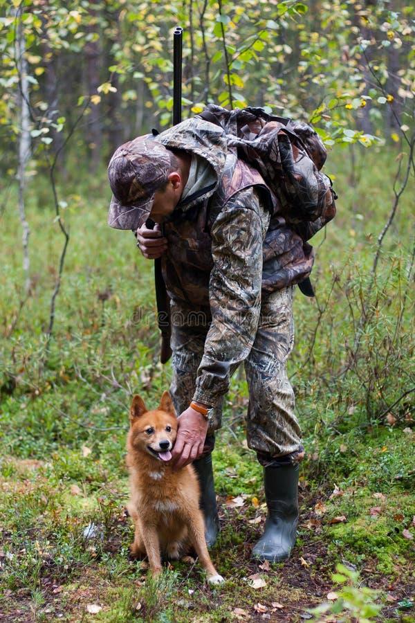 De jager die de hond strijken royalty-vrije stock fotografie