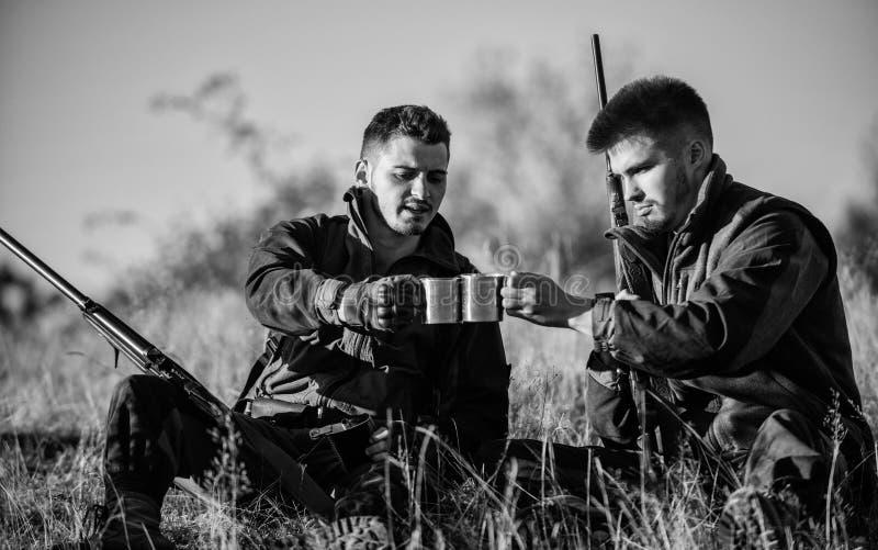 De jagersvrienden genieten van vrije tijd Jagers tevreden met de verwarmende drank van de vangstdrank Rust voor echt mensenconcep stock foto's