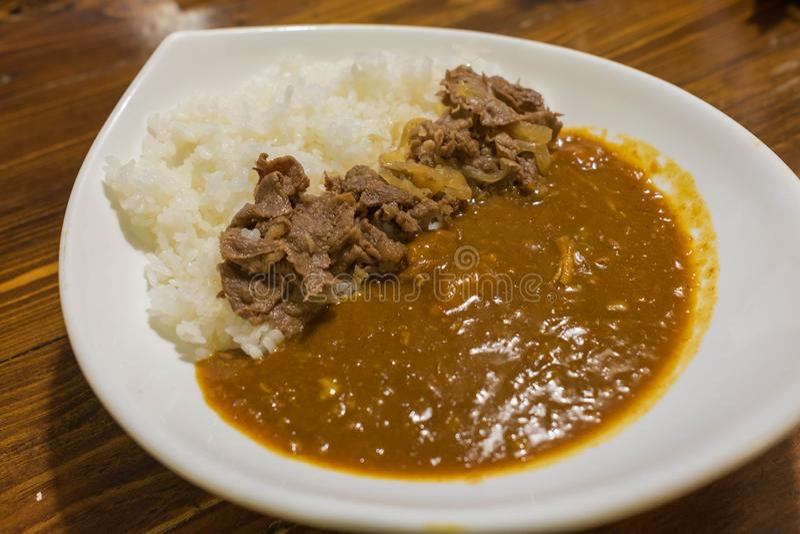 De Japanse die kerrie met rijst met rundvlees en ui wordt bedekt sudderde in een mild zoete op smaak gebrachte saus stock afbeelding
