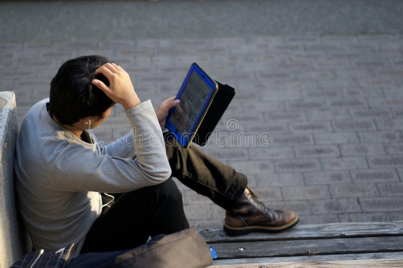 De Japanse mens geniet van zijn tablet op een bank bij het Park Higashi Yuenchi van het Oosten van Kobe in Japan royalty-vrije stock foto
