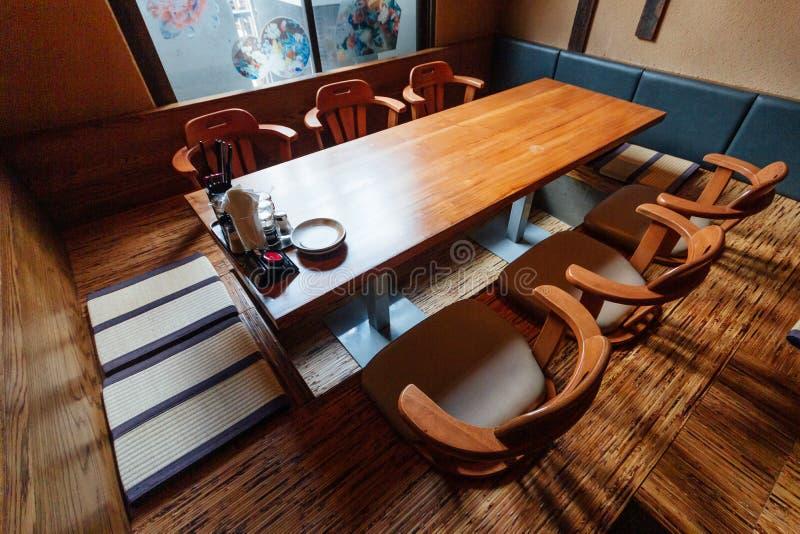 De Japanse stijl ramen restaurant, Lage lijst ter plaatse in centrum met zetels, kleerhangers op de muur royalty-vrije stock foto's
