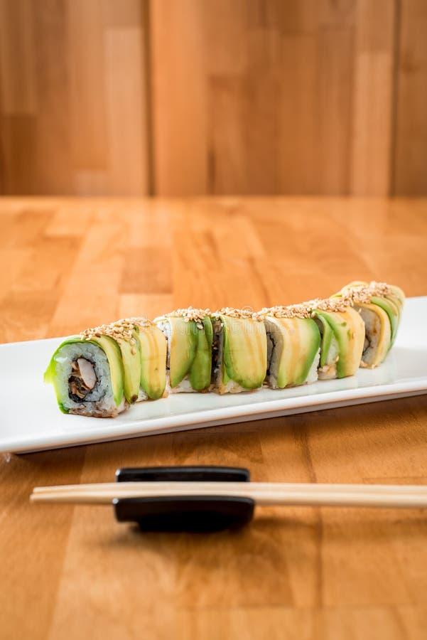 De Japanse sushi rollen groene draak met paling en avocado met gember, kalk, op een witte plaat stock afbeelding