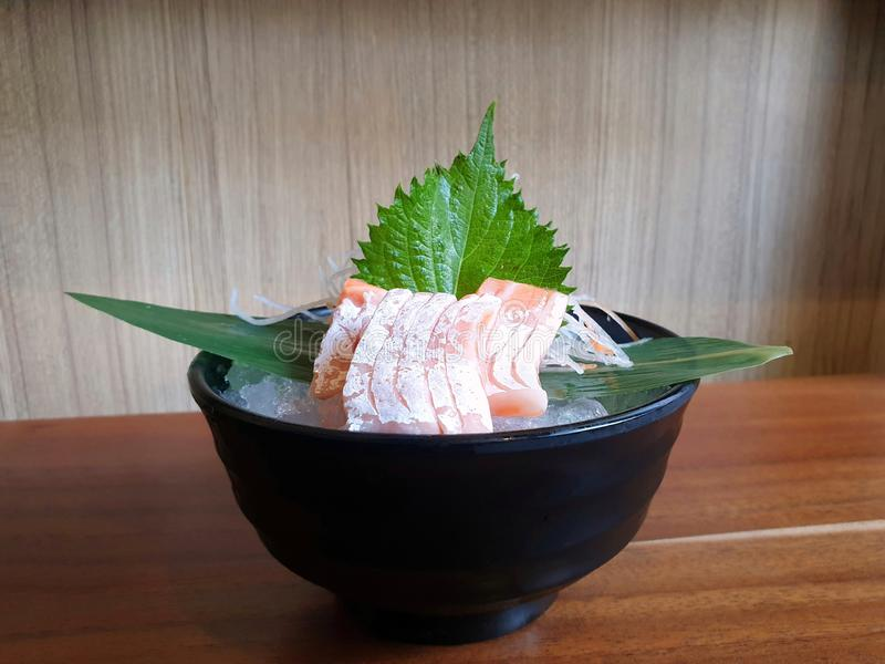 De Japanse voedselstijl, sluit omhoog van de sashimi van de zalmbuik met bamboebladeren op ijs royalty-vrije stock afbeelding