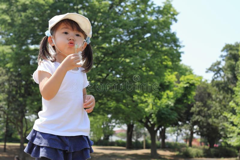De Japanse zaden van de meisjes blazende paardebloem onder de blauwe hemel stock afbeelding