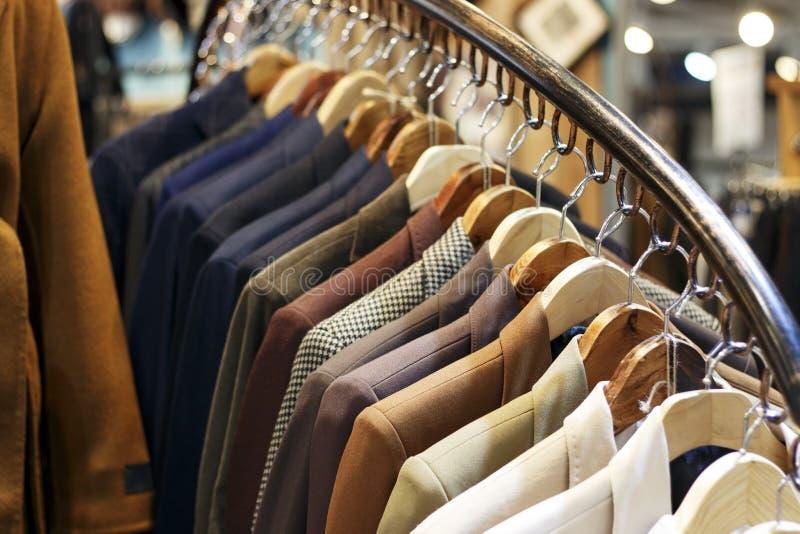 De jasjes van modieuze mensen op hangers in de opslag, close-up stock foto