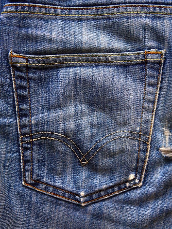 De jeans in eigen zak steken donkere achtergrond stock afbeeldingen